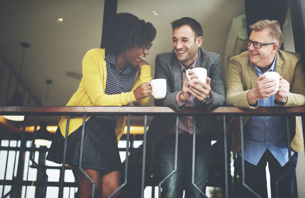 woman-and-two-men-drinking-coffee-on-balcony-of-office-space
